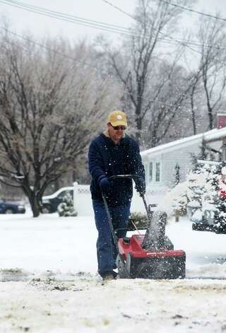 After an overnight snowfall, Lee Lennon Jr. clears his driveway on Sunset Dr. in Derby, Conn. on Tuesday March 19, 2013. Photo: Cathy Zuraw / Connecticut Post