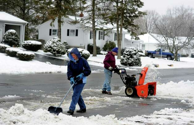 Wanda Frankiewicz and her husband Ted clear a neighbors driveway on Finney St. Ext. in Ansonia, Conn. on Tuesday March 19, 2013. About 3-4 inches of snow fell in the area overnight. Photo: Cathy Zuraw / Connecticut Post