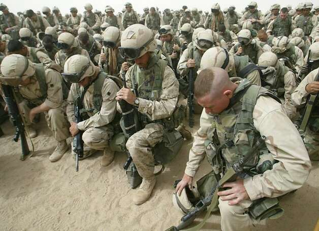 Marines kneel and pray as the 2nd Battalion, 8th Regiment prepares to leave Camp Shoup, north of Kuwait City, in a north-bound direction 20 March, 2003. More than 150,000 allied troops gathered in positions near the Iraqi border to start their advance into southern Iraq. On March 20, 2003 the United States headed a coalition with UK and other forces to invade Iraq.  Photo By Cris Bouroncle/AFP/Getty Images