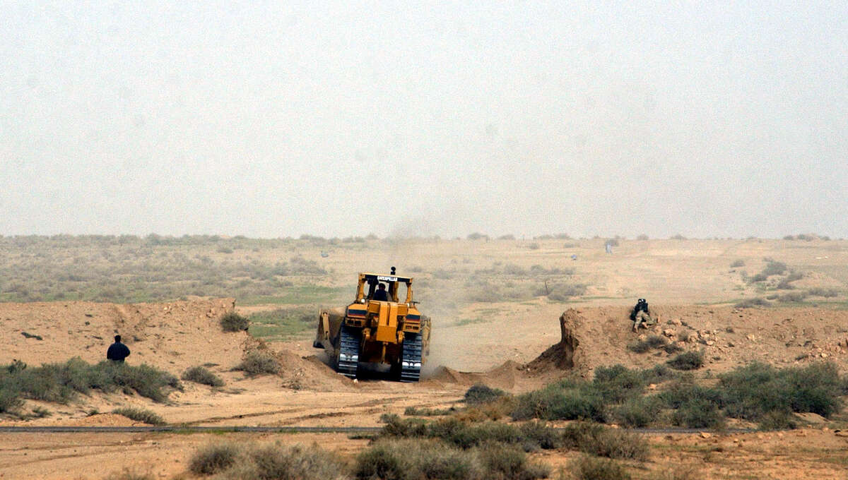 A Kuwaiti backhoe breaks through a 15-foot berm (wall of sand) and into Iraq to create a future path for armed forces vehicles on March 20, 2003, on the Kuwait/Iraq border. Iraq reportedly fired a scud missile toward Kuwait City, which was shot down by a patriot missile.