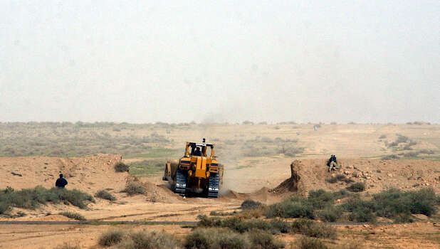 A Kuwaiti backhoe breaks through a 15-foot berm (wall of sand) and into Iraq to create a future path for armed forces vehicles on March 20, 2003, on the Kuwait/Iraq border. Iraq reportedly fired a scud missile toward Kuwait City, which was shot down by a patriot missile. Photo: BAHRAM MARK SOBHANI, SAN ANTONIO EXPRESS NEWS / SAN ANTONIO EXPRESS NEWS