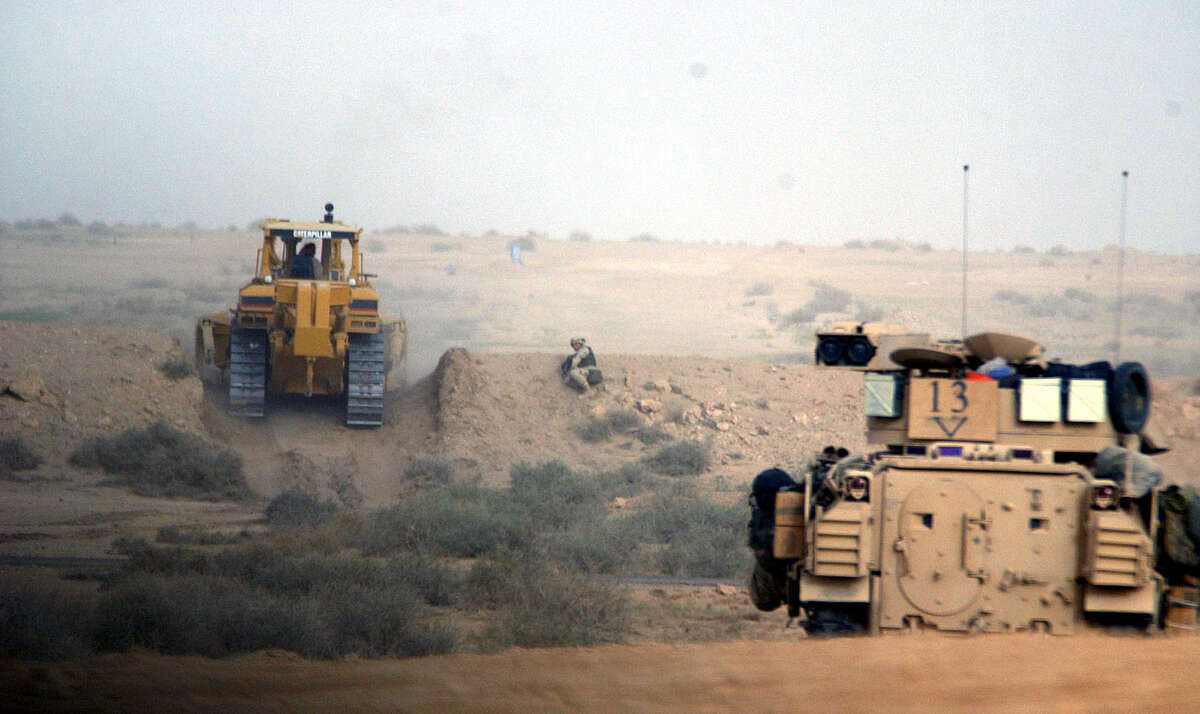 A U.S. soldier keeps watch as a Kuwaiti backhoe breaks through a 15-foot berm (wall of sand) on the Iraqi border to create a path for armed forces vehicles on March 20, 2003, in the northern Kuwaiti desert. Iraq reportedly fired a scud missile toward Kuwait City, which was shot down by a patriot missile.