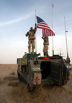 Sgt. Travis Crosby (GA) flies an American flag from an antenna on his crew's armored vehicle in southern Iraq on March 21, 2003. A1C Nick Taylor (OH), right, helps Crosby with the flag.  Photo: BAHRAM MARK SOBHANI, SAN ANTONIO EXPRESS NEWS / SAN ANTONIO EXPRESS NEWS