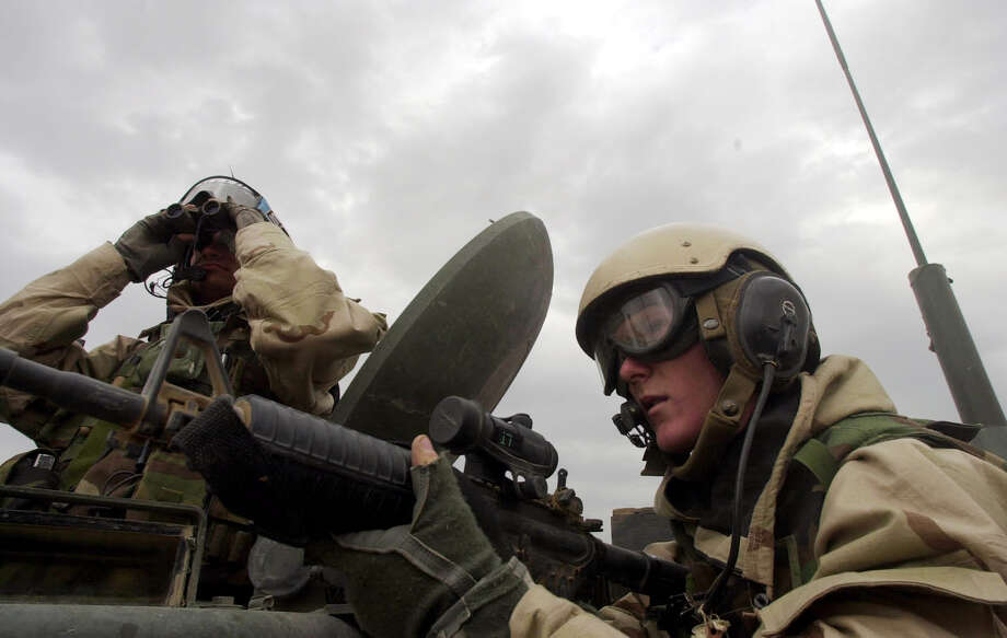 A1C Nick Taylor keeps his gun trained as SSgt. Travis Crosby looks for a possible sniper on March 22, 2003. First brigade troops moving north toward the heart of Iraq had heard reports of a possible sniper in the area as they were traveling through. Photo: BAHRAM MARK SOBHANI, SAN ANTONIO EXPRESS NEWS / SAN ANTONIO EXPRESS NEWS