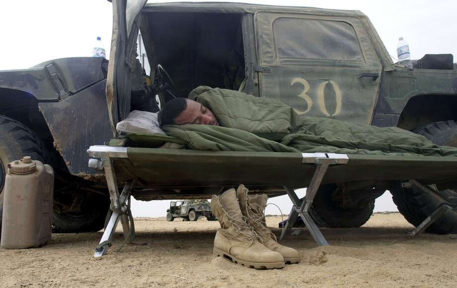 Sgt. Sirvantis Dennis sleeps on a cot outside his vehicle after working overnight in the 1st Brigade's tactical operations center on March 24, 2003, in an area south of Baghdad. Photo: BAHRAM MARK SOBHANI, SAN ANTONIO EXPRESS NEWS / SAN ANTONIO EXPRESS NEWS