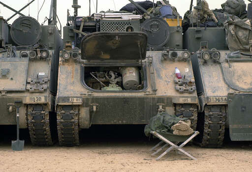 A task force 369 soldier of the 1st Brigade, 3ID sleeps on a cot in front of a row of armored vehicles that make up the 1st Brigade's tactical operations center south of Baghdad in Iraq on March 24, 2003.  Photo: BAHRAM MARK SOBHANI, SAN ANTONIO EXPRESS NEWS / SAN ANTONIO EXPRESS NEWS