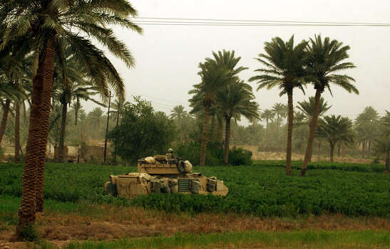 A U.S. tank searches through a lush field near the Euphrates River during a battle with Iraqi soldiers in South Central Iraq on March 25, 2003. U.S. troops were crossing a nearby bridge when Iraqis tried to blow it up. The bridge was damaged but passable.  Photo: BAHRAM MARK SOBHANI, SAN ANTONIO EXPRESS NEWS / SAN ANTONIO EXPRESS NEWS
