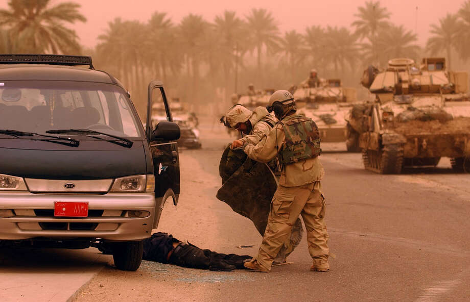 Two U.S soldiers cover a dead Iraqi soldier after a battle near a bridge over the Euphrates River in Southern Iraq on March 25, 2003. The Iraqis reportedly tried to blow up the bridge as U.S. troops drove over it. The bridge sustained damage, but was still passable. Photo: BAHRAM MARK SOBHANI, SAN ANTONIO EXPRESS NEWS / SAN ANTONIO EXPRESS NEWS