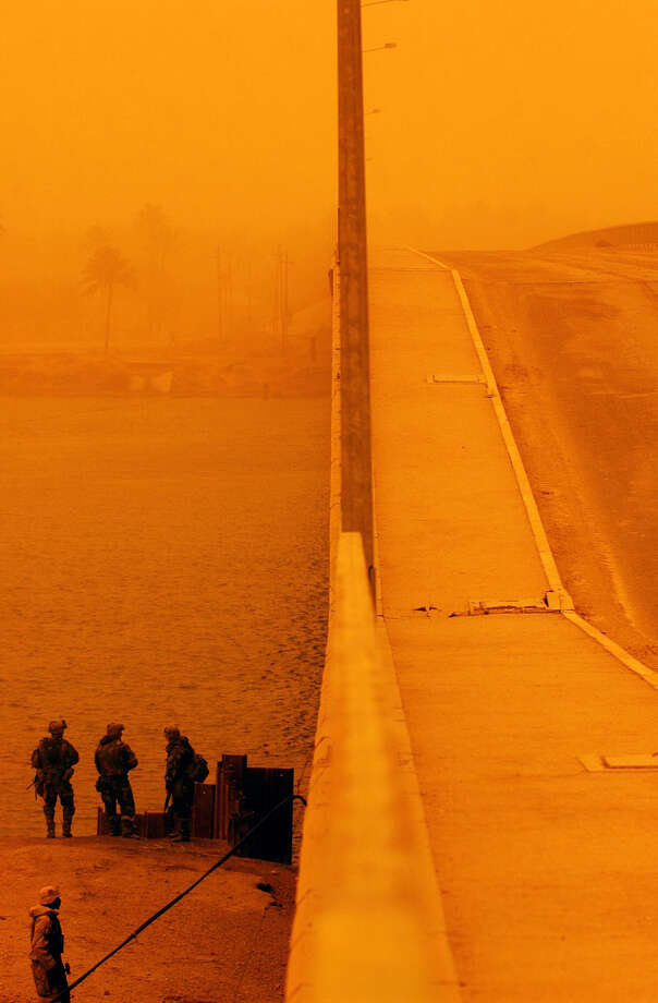 U.S. soldiers watch the waterfront as a Marine reconnaissance group inspects the integrity of a bridge damaged by Iraqi bombs in South Central Iraq on March 25, 2003. The bridge was still passable. Photo: BAHRAM MARK SOBHANI, SAN ANTONIO EXPRESS NEWS / SAN ANTONIO EXPRESS NEWS