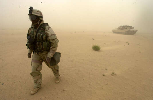 Cpl. Bryan Beard (KS) walks against a stiff wind on guard duty near the Army 1st Battalion, 3rd Infantry Division operations center in Southern Iraq on March 25, 2003. Photo: BAHRAM MARK SOBHANI, SAN ANTONIO EXPRESS NEWS / SAN ANTONIO EXPRESS NEWS