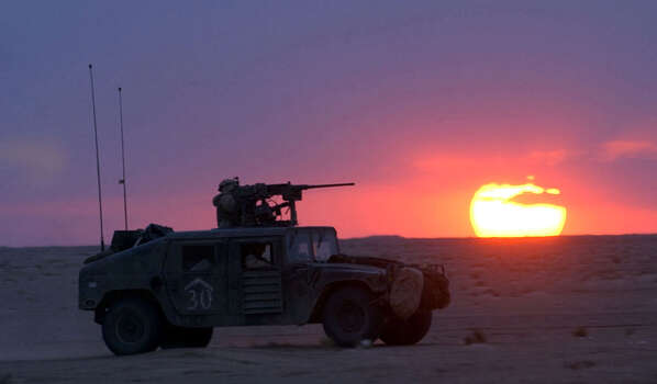A Humvee moves across the desert as the sun sets near the Task Force 3/69 command center in south central Iraq on March 27, 2003. After two days of heavy sandstorm, the skies cleared Thursday with sunny, weather and good visibility.  Photo: BAHRAM MARK SOBHANI, AP / SAN ANTONIO EXPRESS NEWS