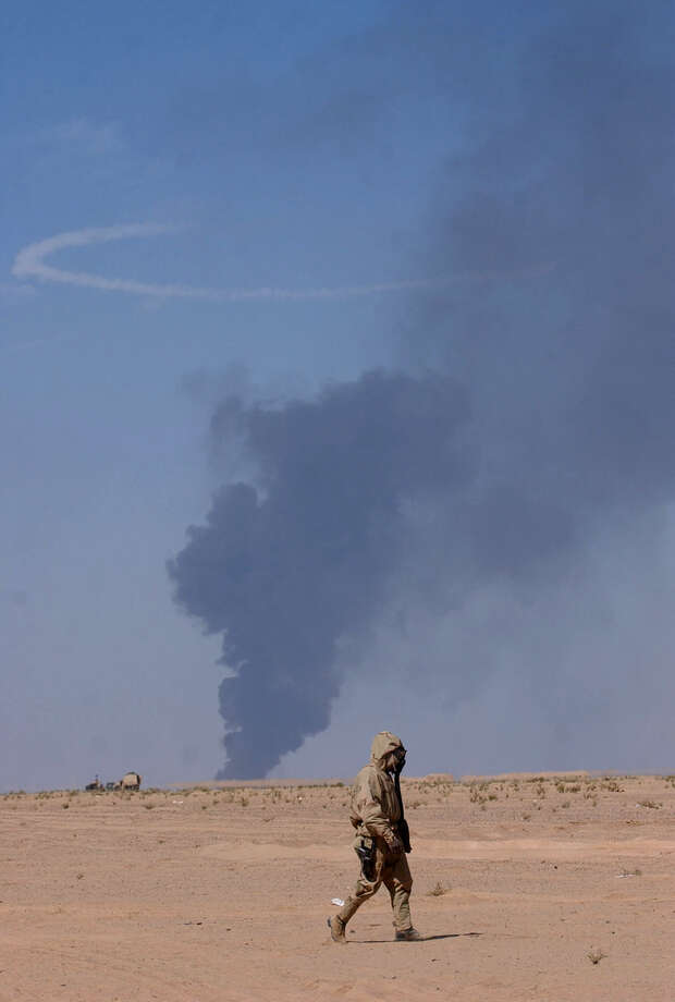 A black cloud of smoke rises in the distance as a soldier with Task Force 3/69 walks to his vehicle in his gas mask on March 28, 2003, in the Iraqi desert. U.S. bombers blasted a series of large fuel storage cells and many surrounding troops were ordered to wear their gas mask until it was certain no chemicals were released into the air.  Photo: BAHRAM MARK SOBHANI, SAN ANTONIO EXPRESS NEWS / SAN ANTONIO EXPRESS NEWS