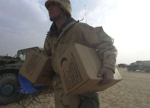 Spc. Joe Perez (GA) carries boxes of MREs (Meals, Ready to Eat) to his vehicle at the Task Force 3-69 assembly area on March 30, 2003, in the South Central Iraqi desert. Each box holds twelve MREs.  Photo: BAHRAM MARK SOBHANI, EXPRESS-NEWS FILE PHOTO / SAN ANTONIO EXPRESS-NEWS