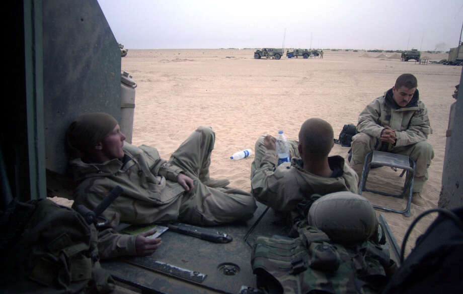 A1C Nick Taylor (OH), Spc. Bryan Slick (MD) and SrA. Dan Housley (Huntsville, TX) bide their time in the late afternoon at the Task Force 3-69 assembly area on March 30, 2003, in the South Central Iraqi desert. For many with the 3rd Infantry Division, this was another day of waiting until until the start of their next objective. Photo: BAHRAM MARK SOBHANI, SAN ANTONIO EXPRESS NEWS / SAN ANTONIO EXPRESS NEWS