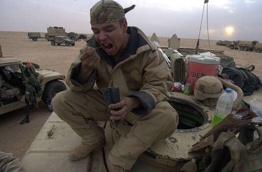 Sgt. Jose Rodriguez (PR) eats an MRE on top of his AVLB (Armored Vehicle Launch Bridge) on March 30, 2003, in the South Central Iraqi desert.  Photo: BAHRAM MARK SOBHANI, SAN ANTONIO EXPRESS NEWS / SAN ANTONIO EXPRESS NEWS