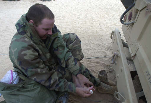 Tech Sgt. Keith Menke (WI) cleans his feet with baby wipes on March 30, 2003, in the South Central Iraqi desert. Menke said he cleans them and changes his socks about every four days.  Photo: BAHRAM MARK SOBHANI, SAN ANTONIO EXPRESS NEWS / SAN ANTONIO EXPRESS NEWS