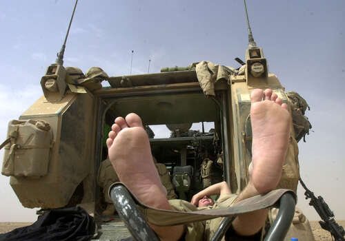Airman Nick Taylor (OH) puts his feet up to rest and air out while resting on a slow day at the Task Force 3-69 assembly area on March 31, 2003, in the South Central Iraqi desert. Monday was one of the hotter days since the beginning of the war, signalling a change in weather. Photo: BAHRAM MARK SOBHANI, SAN ANTONIO EXPRESS NEWS / SAN ANTONIO EXPRESS NEWS