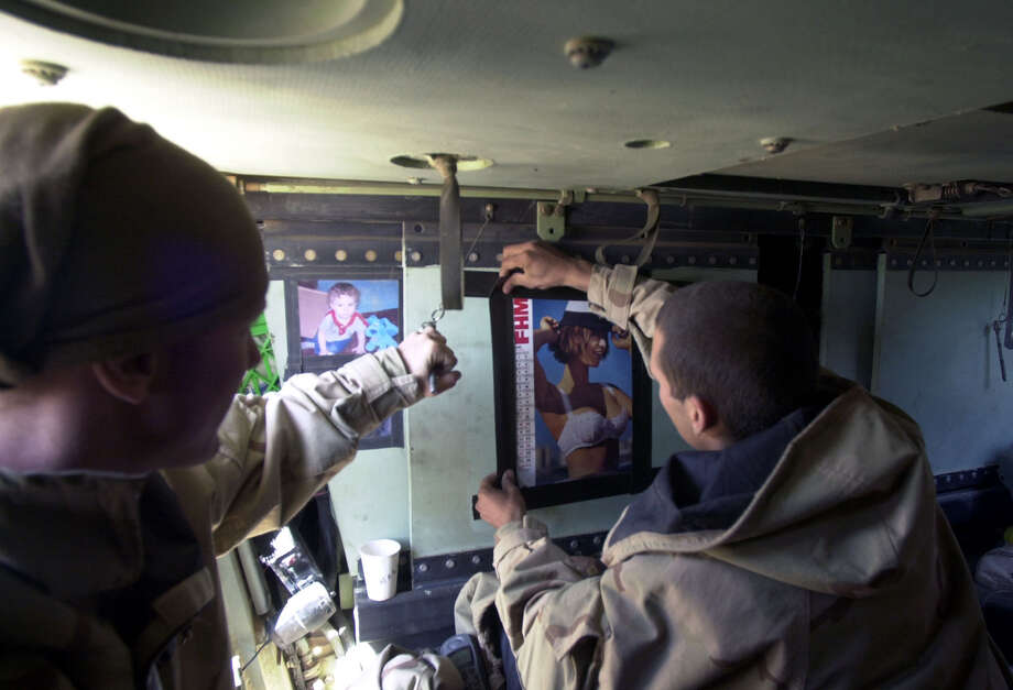 A1C Nick Taylor (OH), left, and SSgt. Travis Crosby (GA) change the month on a pinup calendar in the back of their vehicle at the Task Force 3-69 assembly area on April 1, 2003, in the South Central Iraqi desert. Many thought the war would be winding down at this point. Photo: BAHRAM MARK SOBHANI, SAN ANTONIO EXPRESS NEWS / SAN ANTONIO EXPRESS NEWS