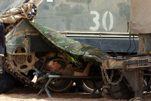 A soldier with the 3rd Infantry Division uses a poncho for shade as he sleeps at the Task Force 3-69 assembly area on March 31, 2003, in the South Central Iraqi desert. Photo: BAHRAM MARK SOBHANI, SAN ANTONIO EXPRESS NEWS / SAN ANTONIO EXPRESS NEWS