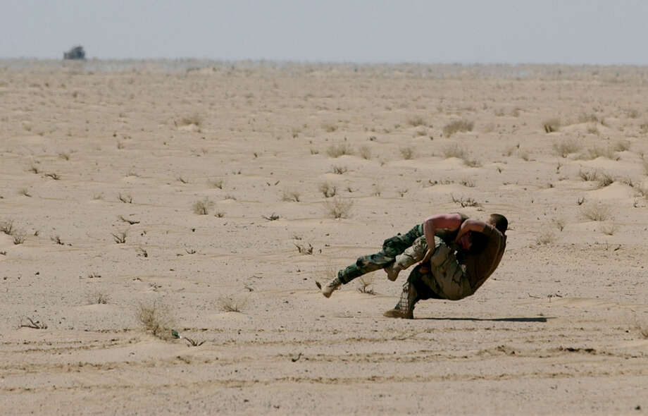 Two soldiers pass the time wrestling in the Iraqi desert while waiting to move north at the Task Force 3-69 assembly area on April 1, 2003, in the South Central Iraqi desert.  Photo: BAHRAM MARK SOBHANI, SAN ANTONIO EXPRESS NEWS / SAN ANTONIO EXPRESS NEWS