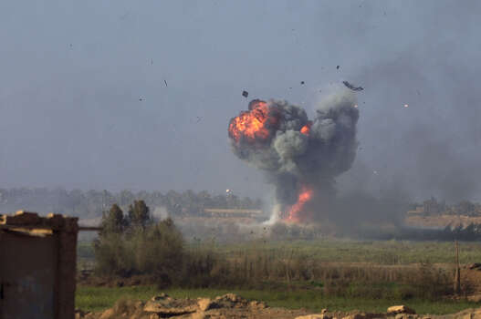 An Iraqi tank explodes after being blasted by an Abrams Tank during a battle for control of a critical bridge north of Karbala on April 2, 2003, in Iraq. Photo: BAHRAM MARK SOBHANI, SAN ANTONIO EXPRESS NEWS / SAN ANTONIO EXPRESS NEWS