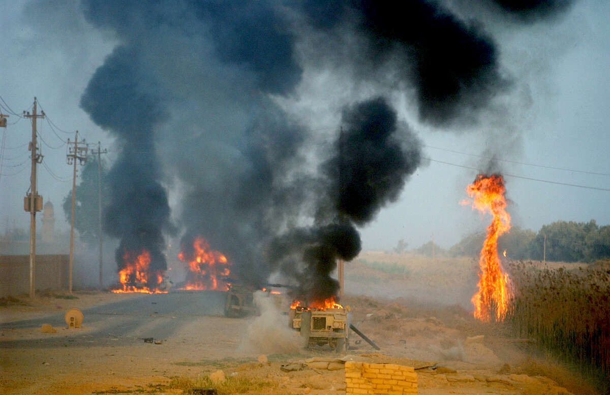 Destroyed Iraqi vehicles burn South of Baghdad Thursday, April 3, 2003 as the 3ID's 1st Brigade move towards Saddam International Airport in Iraq. BAHRAM MARK SOBHANI/STAFF