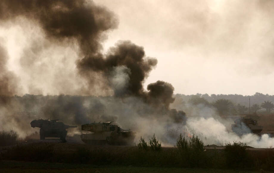 Abrams tanks move forward along a smoke and fire filled roadway during a battle with Iraqi troops for a critical bridge spanning the Euphrates River north of Karbala on April 2, 2003, in Iraq.  Photo: BAHRAM MARK SOBHANI, SAN ANTONIO EXPRESS NEWS / SAN ANTONIO EXPRESS NEWS