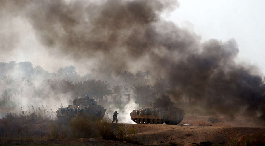 A Task Force 3-69 infantry soldier runs between tanks during a battle for a critical bridge north of Karbala on April 2, 2003, in Iraq. The battle lasted several hours as the U.S. pounded Iraqi troops in the area. Photo: BAHRAM MARK SOBHANI, SAN ANTONIO EXPRESS NEWS / SAN ANTONIO EXPRESS NEWS