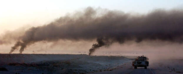 A Bradley fighting vehicle moves past plumes of smoke from destroyed Iraqi army vehicles as Task Force 3-69 pushes north past the Karbala Gap on April 2, 2003, in the South Central Iraqi desert. Photo: BAHRAM MARK SOBHANI, SAN ANTONIO EXPRESS NEWS / SAN ANTONIO EXPRESS NEWS