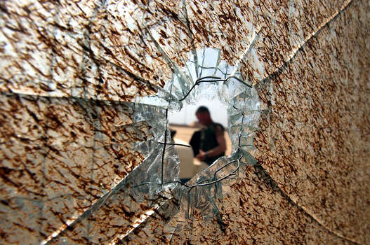 A U.S. soldier is seen through a bullethole in a pane of glass on a hangar door on April 4, 2003, at Saddam International Airport in Iraq. U.S. troops had secured the airport after battling Iraqi forces.  Photo: BAHRAM MARK SOBHANI, AP / SAN ANTONIO EXPRESS NEWS