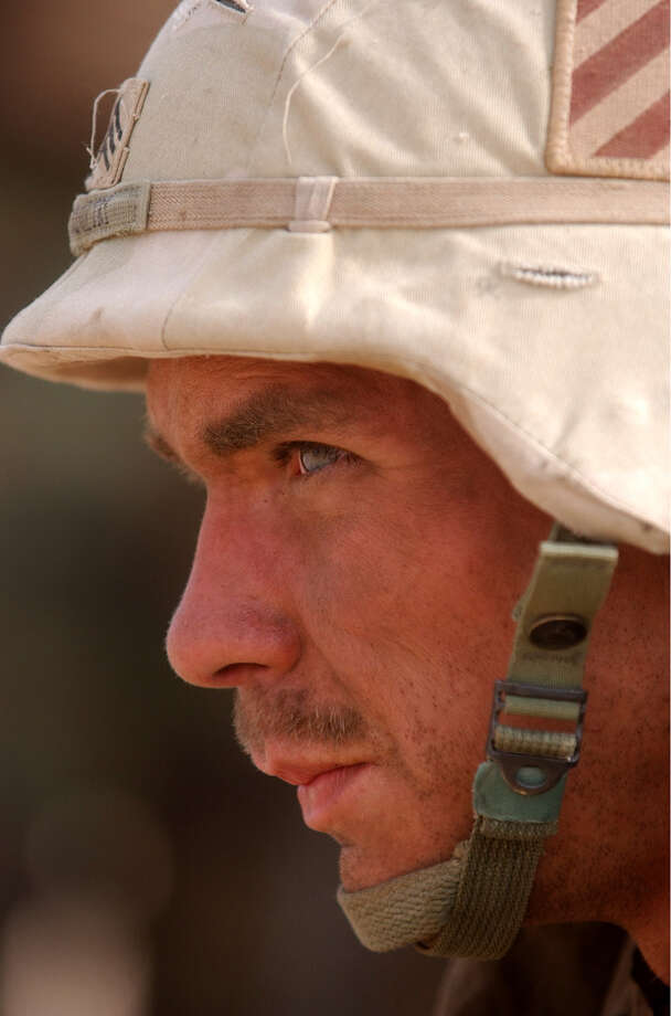Sgt. William Coultry (Americus, GA), a tank commander, pauses by his vehicle after a morning battle at Saddam International Airport Friday, April 4, 2003, in Iraq. Photo: BAHRAM MARK SOBHANI, SAN ANTONIO EXPRESS NEWS / SAN ANTONIO EXPRESS NEWS