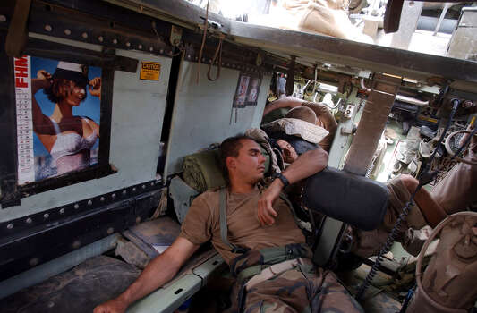 Air Force Cpt. Shad Magann, SSg. Travis Crosby, and Spc Bryan Slick sleep in the back of an armored vehicle after an overnight and early morning fight for control of Saddam International Airport on April 4, 2003, in Iraq. Photo: BAHRAM MARK SOBHANI, SAN ANTONIO EXPRESS NEWS / SAN ANTONIO EXPRESS NEWS