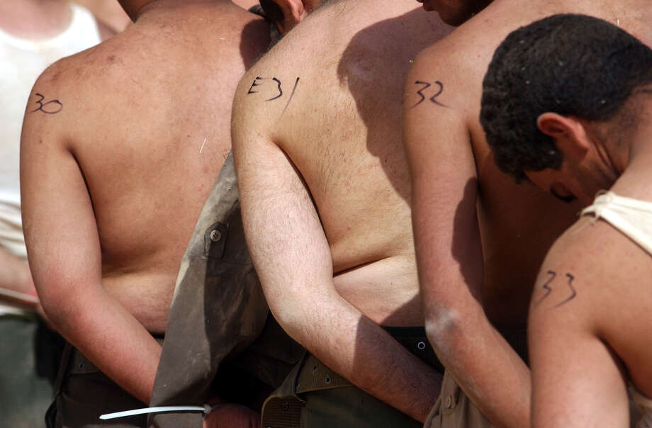 Iraqi POWs are numbered with a marker as they are processed at a hangar on April 4, 2003, at Saddam International Airport in Iraq. Photo: BAHRAM MARK SOBHANI, SAN ANTONIO EXPRESS NEWS / SAN ANTONIO EXPRESS NEWS