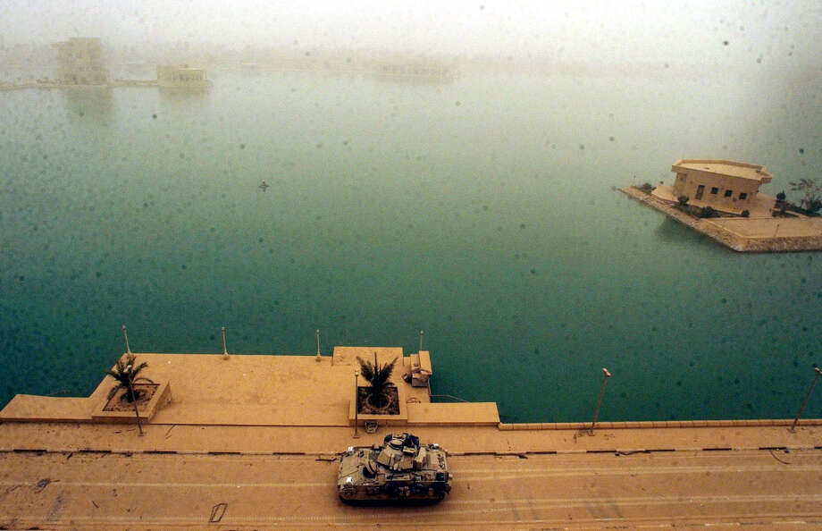 A Bradley guards the back side of one of Saddam Hussein's palaces, which is surrounded by a lake on April 7, 2003, in western Baghdad. U.S. forces overtook the compound in a morning effort.  Photo: BAHRAM MARK SOBHANI, SAN ANTONIO EXPRESS NEWS / SAN ANTONIO EXPRESS NEWS
