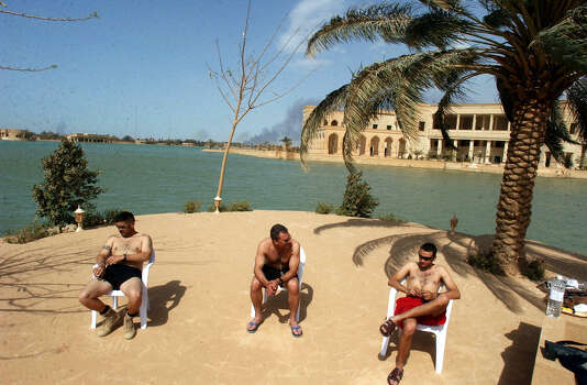 Air Force SSt. Michael Cmelik, left Capt. Shad Magann and SSt. Travis Crosby sunbathe lakeside during downtime on April 10, 2003, at one of Saddam Hussein's palace in western Baghdad.  Photo: BAHRAM MARK SOBHANI, SAN ANTONIO EXPRESS NEWS / SAN ANTONIO EXPRESS NEWS