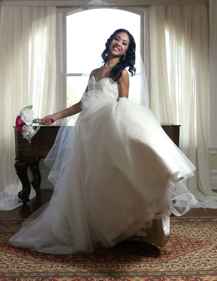 Vanessa Arauco wears a high-low hemline chiffon-layered gown with a plunging neckline and shoulder flounces, $1,595 by Pronovias; her hair is accessorized with a rhinestone-studded elastic headband, $375, by Les Accessoires, both from Bridal Galleria of Texas, (210) 341-5752. Her crystal drop earrings, $42, and silver metallic blinged sandals, $70, are from the Bridal Salon of San Antonio, (210) 828-7931. Photo: Helen L. Montoya, San Antonio Express-News / ©2013 San Antonio Express-News