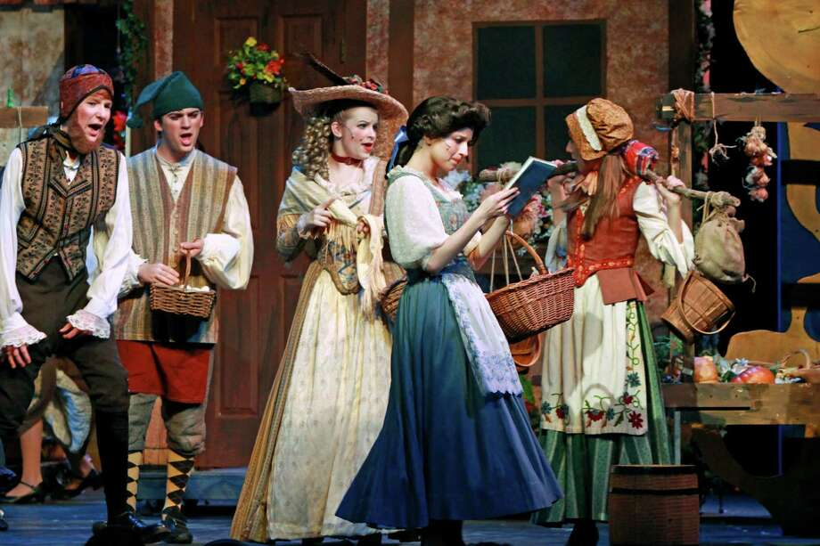 """Belle (played by Christy Coco) is unaware of the surrounding townspeople as she reads during a scene from""""Beauty & the Beast,"""" which opens this week at New Canaan High School. Photo: Contributed"""