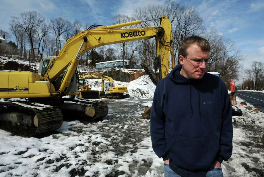 John Wardowski stands near a hillside that was blasted to make room for a commercial building along the River Rd in Shelton, Conn.  Wardowski's house, seen behind him, is on Turner Road, a short, private road overlooking the River Road. Photo: Cathy Zuraw / Connecticut Post
