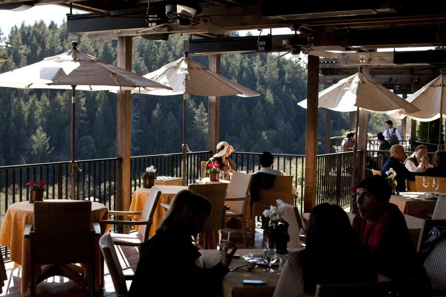 Patrons dine and drink on the deck overlooking the valley at Auberge du Soleil.