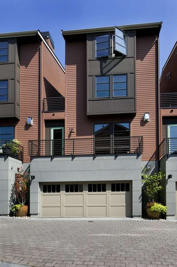 Exterior of 3213 W. Lynn St. The 2,500-square-foot condominium townhouse, built in 2009, has three bedrooms, 2.75 bathrooms, a private elevator, a gated courtyard, travertine floors, two fireplaces and a storefront office. It's listed for $799,000. Photo: Courtesy Kathleen Madsen/Brazen Sothebys International Realty