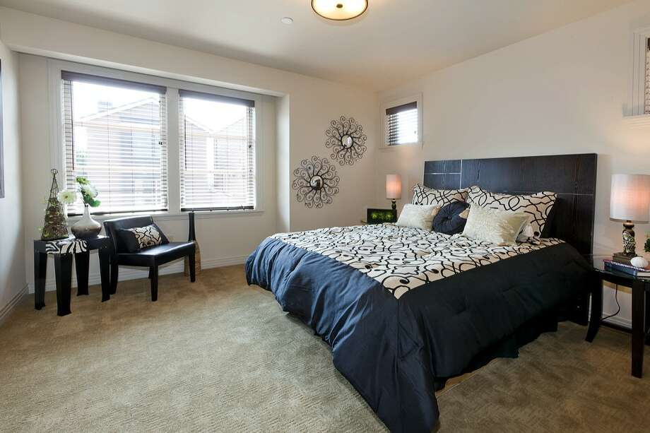 Bedroom of 3213 W. Lynn St. The 2,500-square-foot condominium townhouse, built in 2009, has three bedrooms, 2.75 bathrooms, a private elevator, a gated courtyard, travertine floors, two fireplaces and a storefront office. It's listed for $799,000. Photo: Courtesy Kathleen Madsen/Brazen Sothebys International Realty