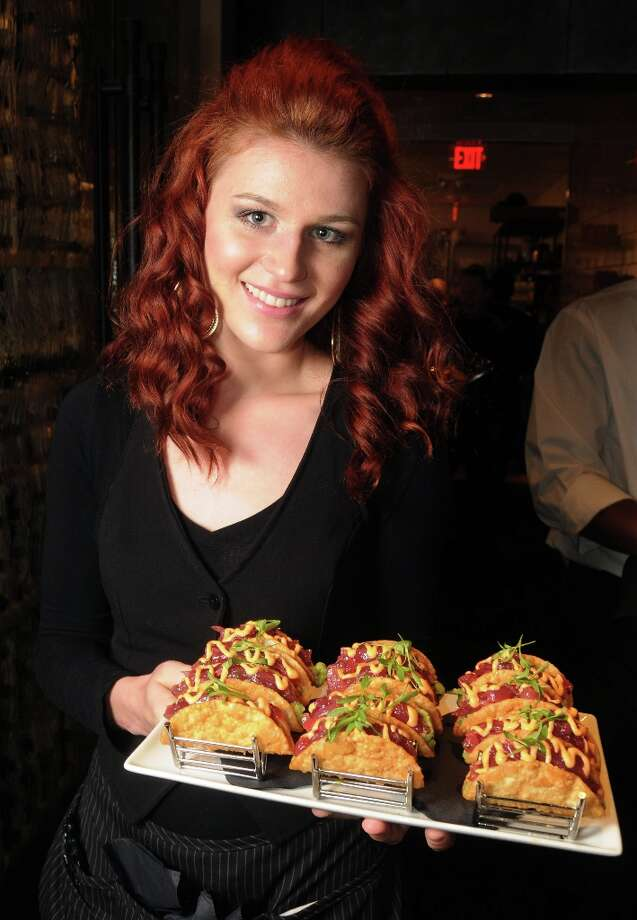 Server Sasha Grishina with a tray of tacos at the grand opening party at Del Frisco's Grille at West Ave. Thursday March 14, 2013. Photo: Dave Rossman / © 2013 Dave Rossman