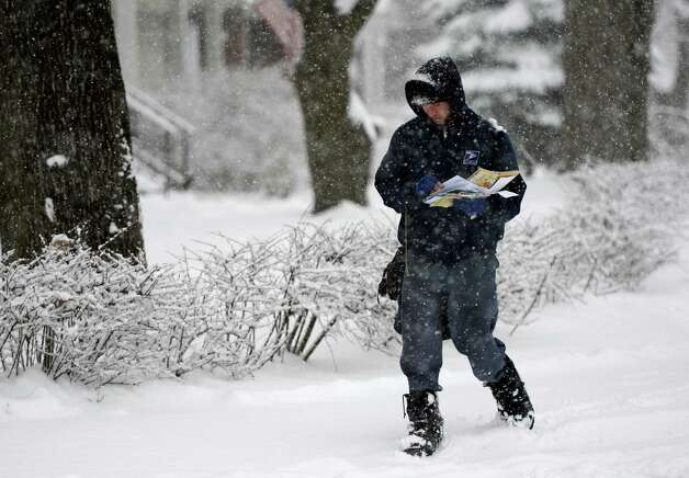 U. S. Mail letter carrier Chris Butkereit walks through the snow and slush to make sure the mail is delivered on his route on Eastern Parkway March 19, 2013,  in Schenectady, N.Y.(Skip Dickstein/Times Union) Photo: SKIP DICKSTEIN