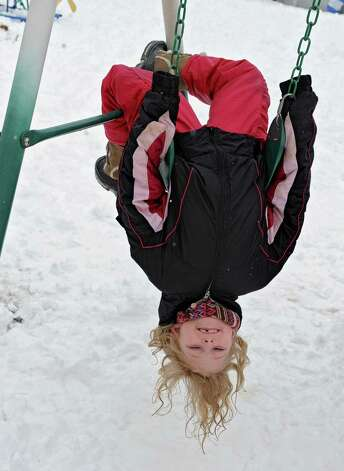 Natalia Daparma, 7, of Victory hangs upside down on a swing as she plays in the snow at her home on Tuesday, March 19, 2013 in Victory, N.Y. (Lori Van Buren / Times Union) Photo: Lori Van Buren