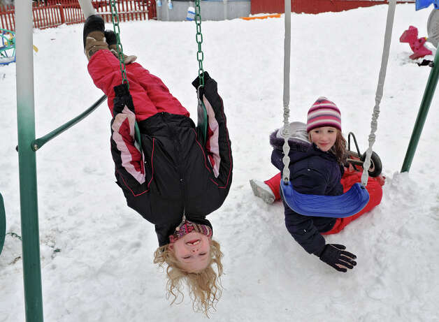 Natalia Daparma, 7, of Victory hangs upside down on a swing while her friend Amber Willette, 13, of Victory watches on Tuesday, March 19, 2013 in Victory, N.Y. (Lori Van Buren / Times Union) Photo: Lori Van Buren
