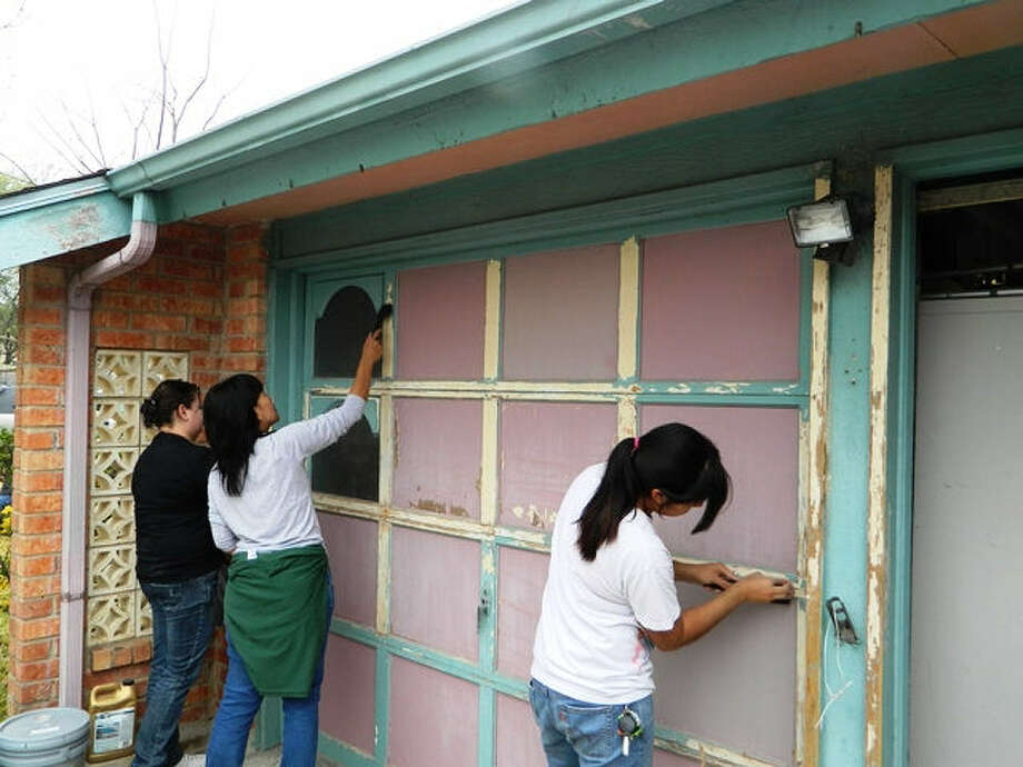 "Live Oak's Parkour, Skate and Bike Association (PSBA) members and supporters Susana Romero, Wilma Gibson and Rachel Garcia scrape old paint off a garage door and apply a new coat during the group's ""Crash A House"" effort Saturday. Photo: Tamara Pearis / For The NE Herald"