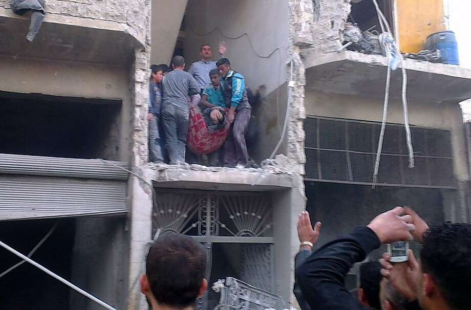 """Citizen journalism image provided by Aleppo Media Center AMC which has been authenticated based on its contents and other AP reporting, Syrian citizens carry an injured man from a damaged building that was hit by a Syrian forces airstrike, on the al-Marjeh neighborhood, of Aleppo, Syria, Tuesday March 19, 2013. Syria's information minister says a chemical weapon fired by rebels on a village in the north of the country is the """"first act"""" by the opposition interim government announced in Istanbul. (AP Photo/Aleppo Media Center, AMC) Photo: Hoep, Associated Press"""