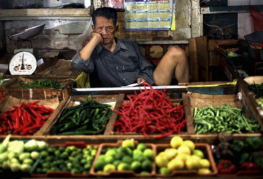 Buy something already!The vegetables aren't getting any fresher. (Market in Jakarta.) Photo: Dita Alangkara, Associated Press
