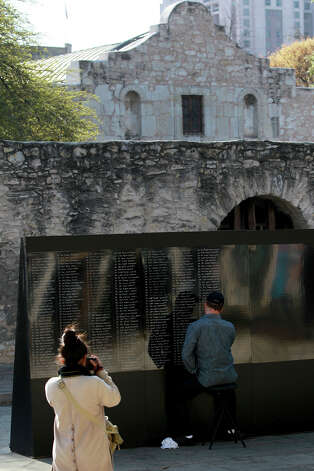 Ron White (seated, facing away) writes names down in front of the Alamo Tuesday March 19, 2013 of fallen soldiers who fought in Afghanistan. White, a navy veteran, is writing the names down from memory to honor Americans who died serving their country. White said he is also hoping to raise awareness for the Wounded Warrior Project. White said his next stop is Times Square in New York. Photo: JOHN DAVENPORT, SAN ANTONIO EXPRESS-NEWS / ©San Antonio Express-News/Photo may be sold to the public