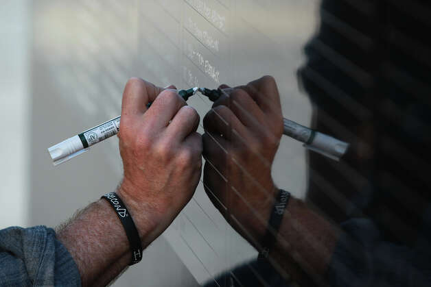 Ron White writes names down in front of the Alamo Tuesday March 19, 2013 of fallen soldiers who fought in Afghanistan. White, a navy veteran, is writing the names down from memory to honor Americans who died serving their country. White said he is also hoping to raise awareness for the Wounded Warrior Project. White said his next stop is Times Square in New York. Photo: JOHN DAVENPORT, SAN ANTONIO EXPRESS-NEWS / ©San Antonio Express-News/Photo may be sold to the public
